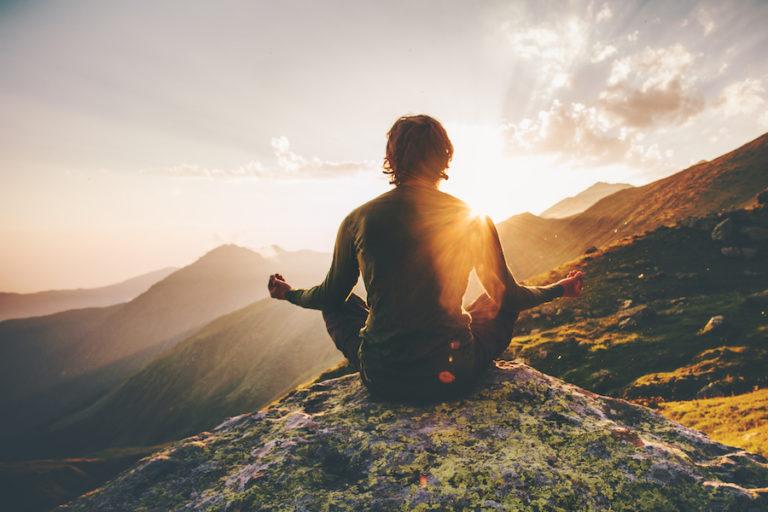man meditating mountain